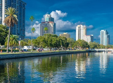 A shot of the St. Petersburg Bay from the water, with clear water, palm trees and tall buildings